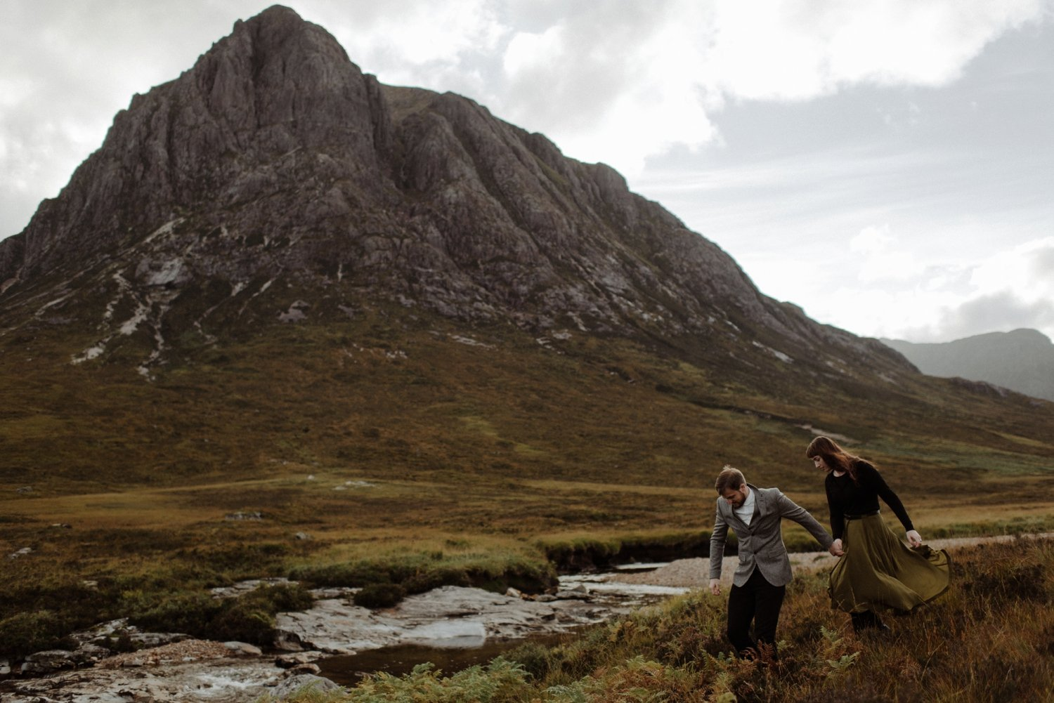 couple walking with mountain in background