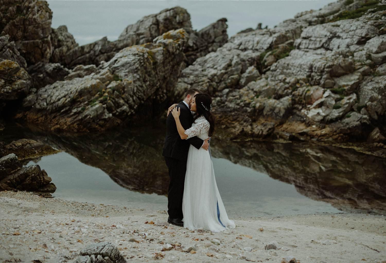 bride and groom hugging on beach