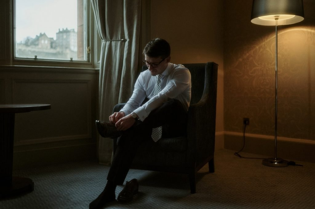 Groom putting shoes on in Edinburgh, one of the best places to elope in Scotland.
